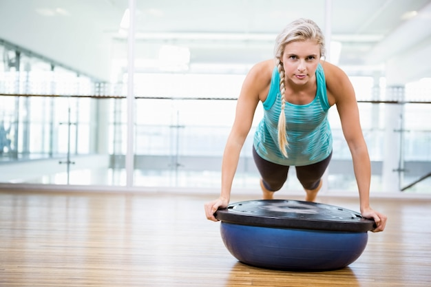 Fit blonde doing push up on bosu ball in fitness studio