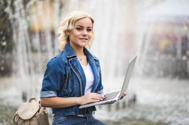 Подходит студентка блондинка девушка работает на своем портативном компьютере возле фонтана в городе в день