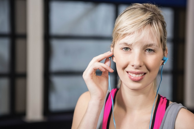Fit blonde listening to music at the gym