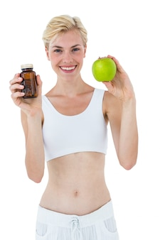 Fit blonde woman holding medicine and green apple