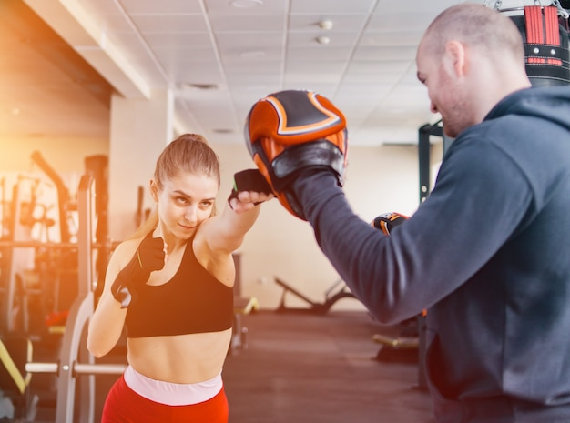 男性トレーナーと金髪の女性のトレーニングパンチを合わせます。ジムで。パンチを行使するカップル