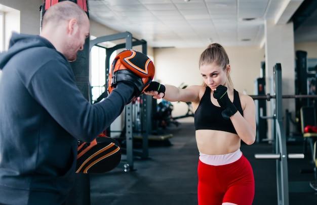 男性トレーナーとフィットブロンドの女性トレーニングパンチ