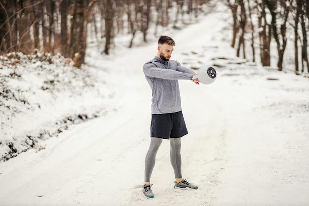 森の中の雪道に立って冬にケトルベルを振るボディービルダーに合いましょう。ボディービルの練習、冬のフィットネス、屋外のフィットネス