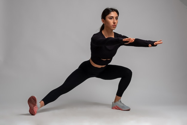 Fit brunette doing bodyweight side lunges on grey wall