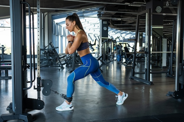 Fit brunette performing lunges on cable crossover at gym