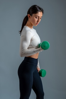 Fit brunette performing upper body workout with dumbbells on grey wall
