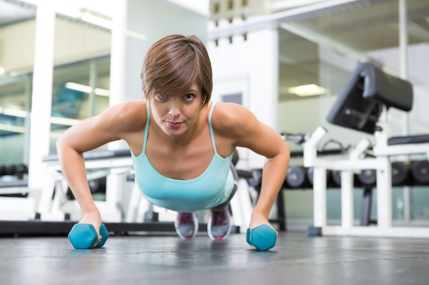 Fit brunette in plank position with dumbbells