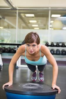 Fit brunette using bosu ball in plank position