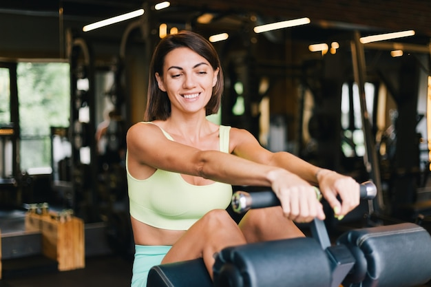 Fit caucasian beautiful woman in fitting sport wear at gym on abs core machine happy smiling