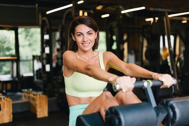 Montare la bella donna caucasica nell'adattare l'abbigliamento sportivo in palestra sulla macchina per addominali sorridenti