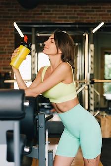 Una bella donna caucasica in forma che indossa abbigliamento sportivo in palestra tiene uno shaker di proteine protein