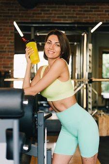 Fit caucasian beautiful woman in fitting sport wear at gym holds protein shaker