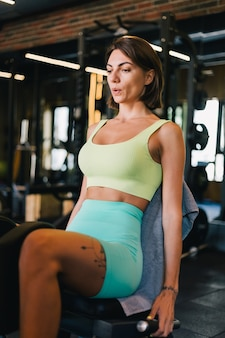 Fit caucasian beautiful woman in fitting sport wear at gym at leg machine working out