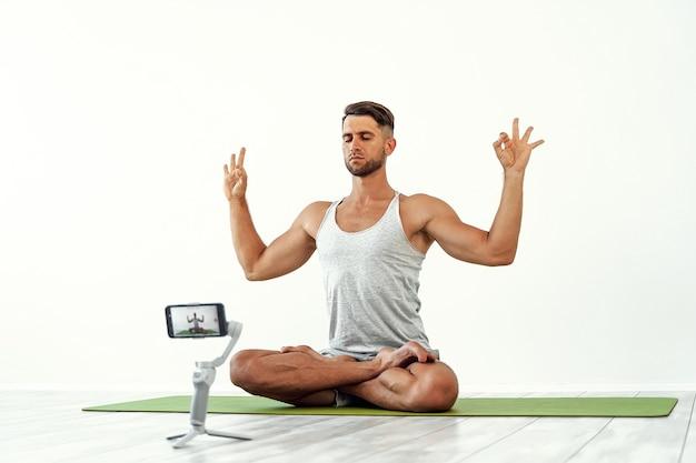 ブログを録音したり、ヨガのトレーニングをストリーミングしたりする白人男性に合う
