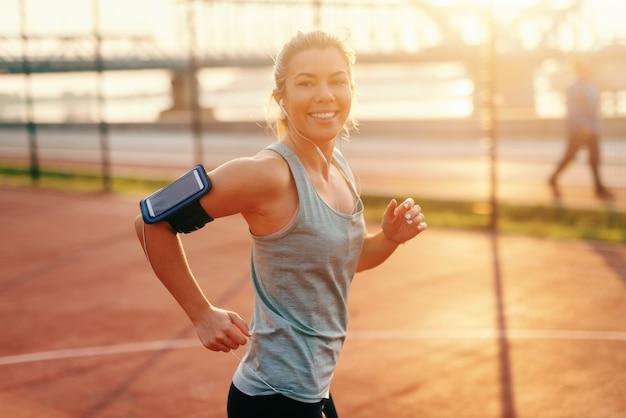 早朝ジョギング白人笑顔の金髪女性に合います。腕の周りの電話ケースと耳の中のイヤホン。