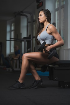 A fit caucasian woman doing biceps lifts with weights in a gym. she is strong and determined. she is sitting on a bench