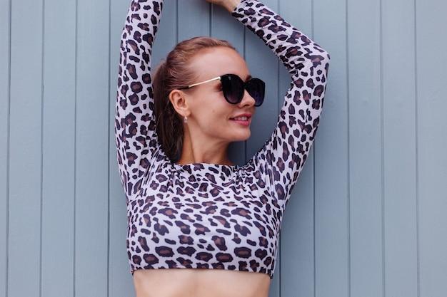 Подходящая кавказская женщина в леопардовом купальнике и солнцезащитных очках на серой стене