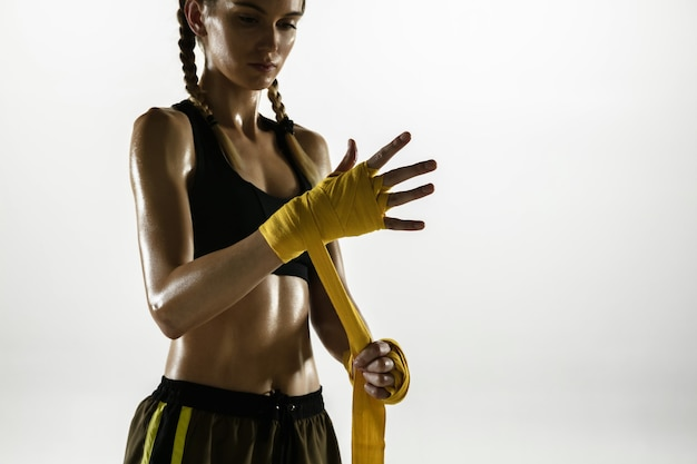 白い背景で隔離のスポーツウェアボクシングに白人女性をフィットさせます。