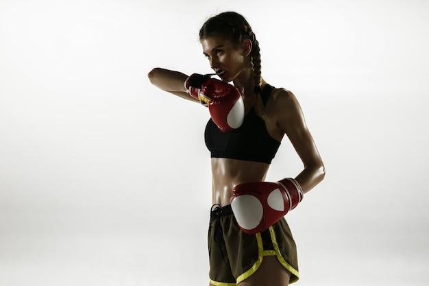白いスタジオの背景に分離されたスポーツウェアボクシングに白人女性を合わせる