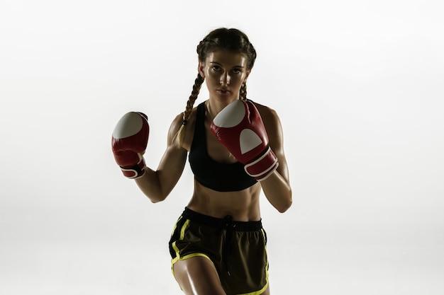 흰색 벽에 고립 된 스포츠 복싱에 맞는 백인 여자. 초보자 여성 백인 권투 선수 훈련 및 운동과 행동 연습. 스포츠, 건강한 라이프 스타일, 운동 개념.