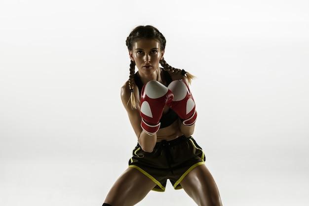 白い壁に分離されたスポーツウェアボクシングに白人女性をフィットさせます。初心者の女性の白人ボクサーのトレーニングと動きと行動の練習。スポーツ、健康的なライフスタイル、動きのコンセプト。