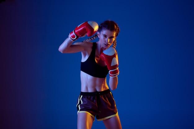 ネオンの光の青い背景の上のスポーツウェアボクシングに白人女性を合わせます。