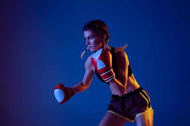 Fit caucasian woman in sportswear boxing on blue studio background in neon light