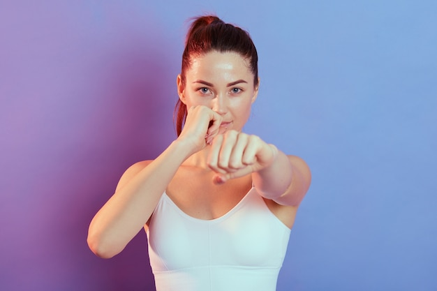 Fit caucasian woman in sportswear boxing on color background in neon light, attractive female boxer working out and training. sport, healthy lifestyle, movement.