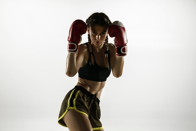 Fit caucasian woman in sportswear boxing isolated on white  wall. novice female caucasian boxer training and practicing in motion and action. sport, healthy lifestyle, movement concept.