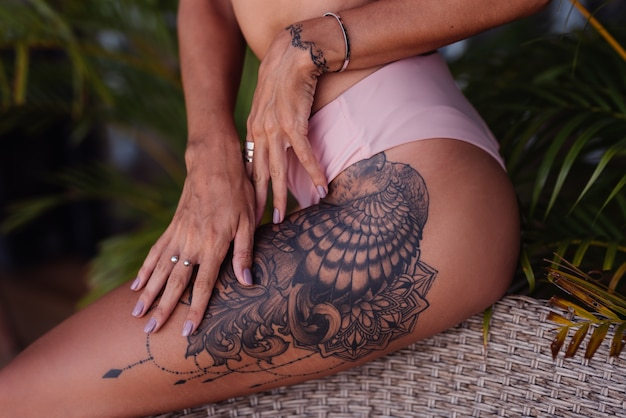 Fit caucasian woman tanned with large tattoo on leg in bikini wearing rings, tropical leaves around