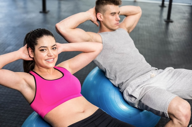 Fit couple doing abdominal crunches on fitness ball at gym