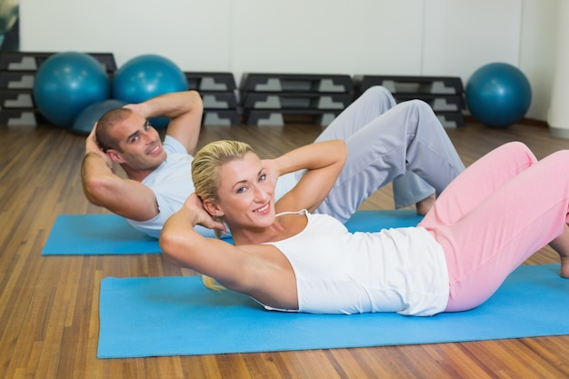 Fit couple doing abdominal crunches at the gym