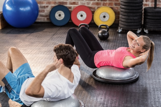 Fit couple doing abdominal crunches