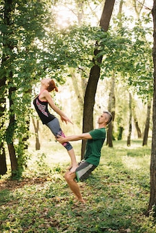 Fit couple doing acroyoga balance in park