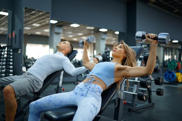 체육관에서 아령으로 운동을 하는 맞는 커플