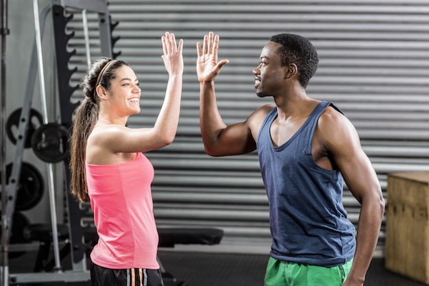 Fit couple doing high five at crossfit gym