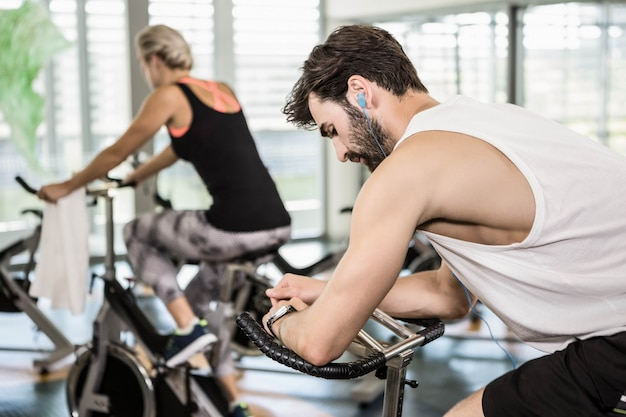 Fit couple on exercise bikes at the gym