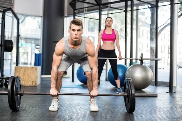 Fit couple lifting barbell at gym