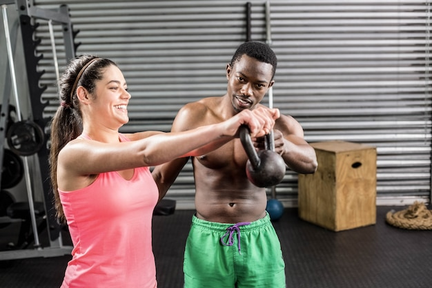 Fit couple lifting dumbbells at crossfit gym