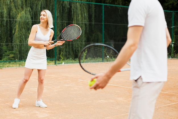 Fit couple playing tennis together