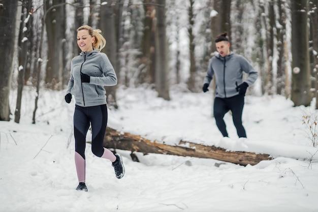 눈 덮인 겨울 날 숲에서 경주에 맞는 커플. 관계, 건강한 생활 방식, 성공