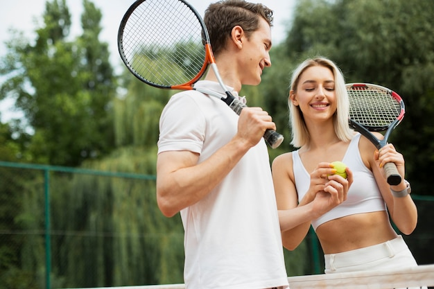 Fit couple ready to play tennis