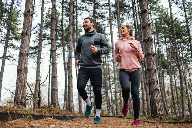 Fit couple running trough woods at autumn and preparing for marathon