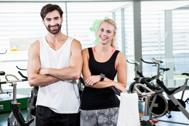 Fit couple smiling at the camera with arms crossed at the gym