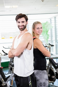 Fit couple standing back to back with arms crossed at the gym