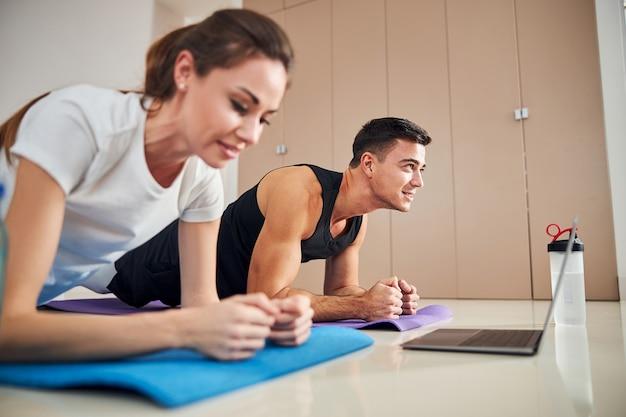 운동하는 동안 판자 위치에 서 있는 맞는 커플
