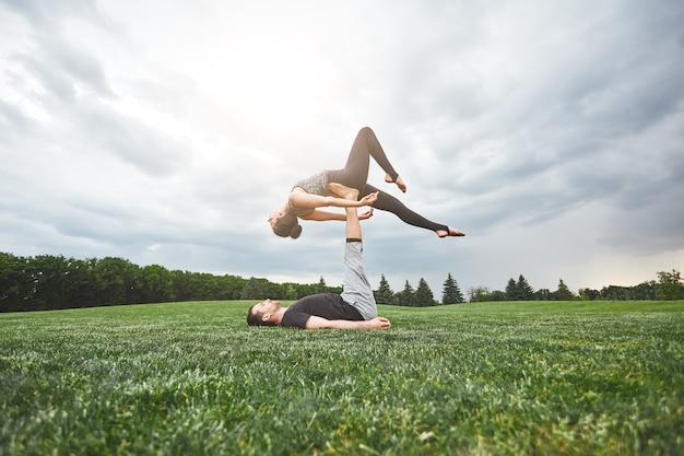 맞는 커플 강한 젊은 남자 잔디에 누워 그의 다리 건강에 균형 여자