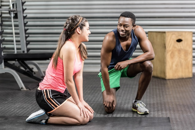 Fit couple taking a break at crossfit gym