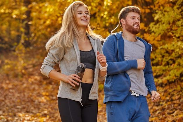 야외에서 화창한 가을 날, 운동 백인 남자와 여자 조깅 커플 훈련을 맞습니다. 적극적인 커플 조깅