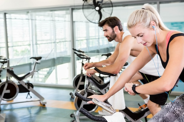 Fit couple using exercise bikes at the gym